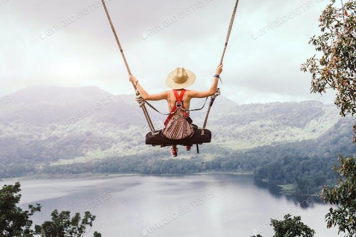 Beautiful girl enjoying freedom on swing in Bali, Indonesia