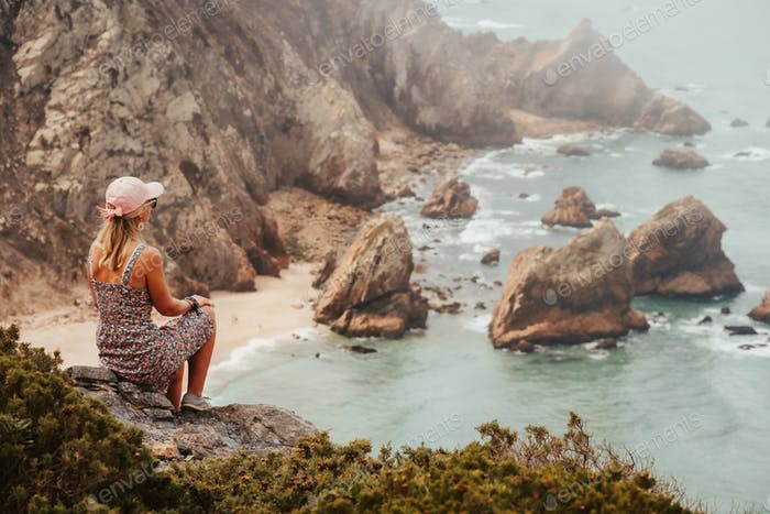 Beautiful tourist women enjoying impressive Praia da Ursa Beach in morning light. Surreal scenery of