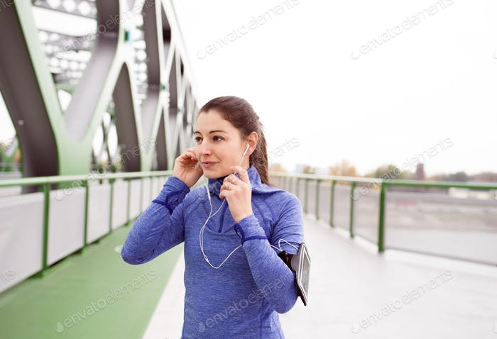 Young woman running in the city on green steel bridge