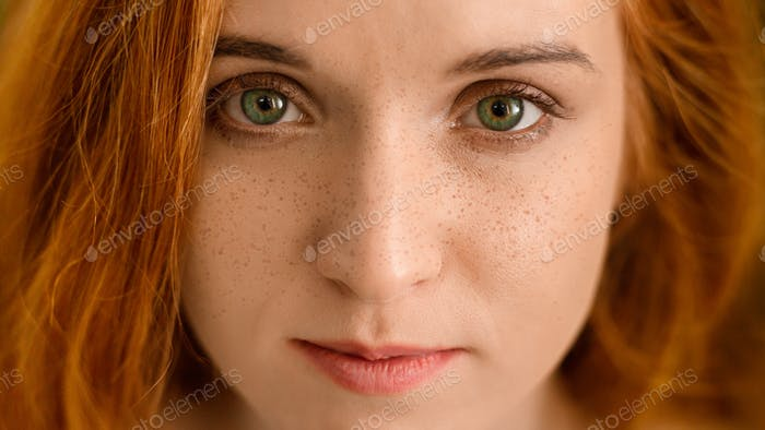 Young redhead woman with freckles looking at camera