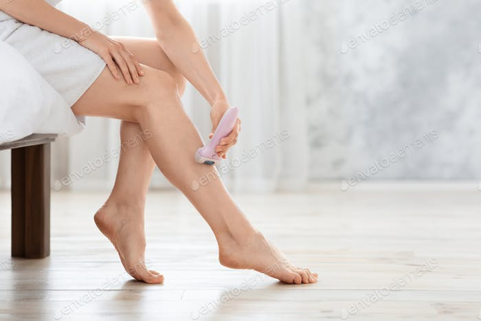 Unrecognizable young woman removing hair on legs with epilator