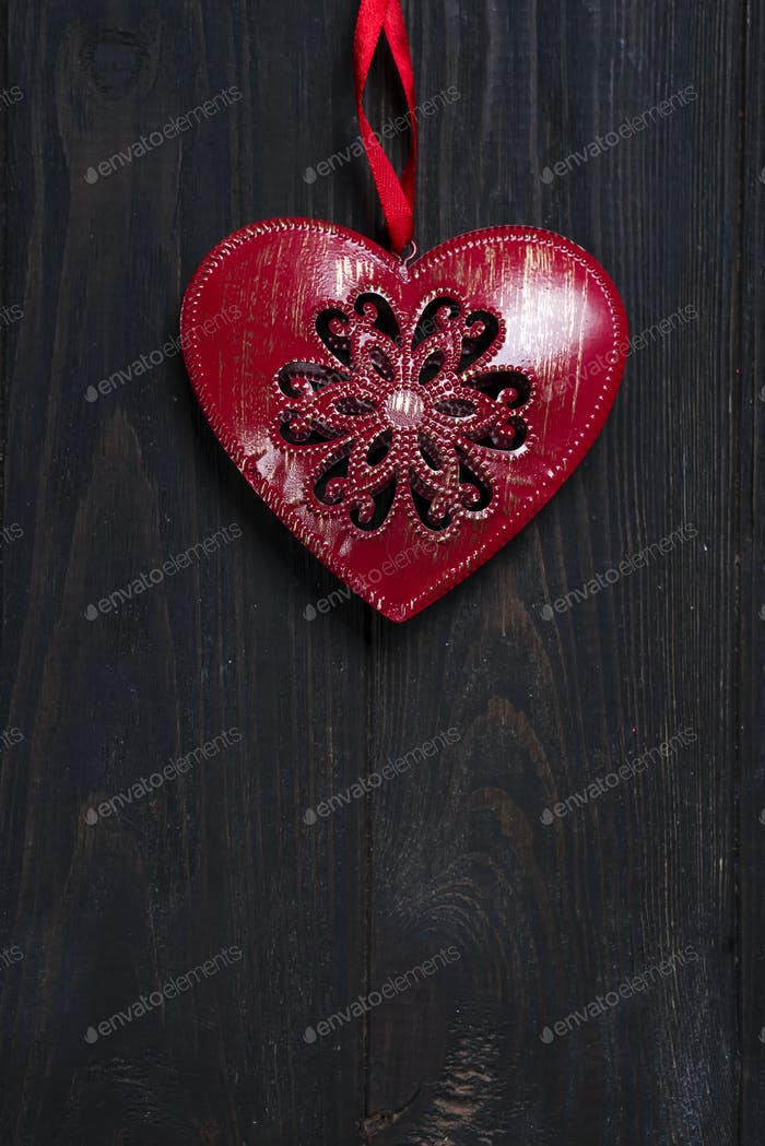 iron red heart on wooden background.