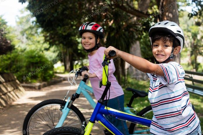 Porträt von lächelnden Kindern stehen mit Fahrrad im Park