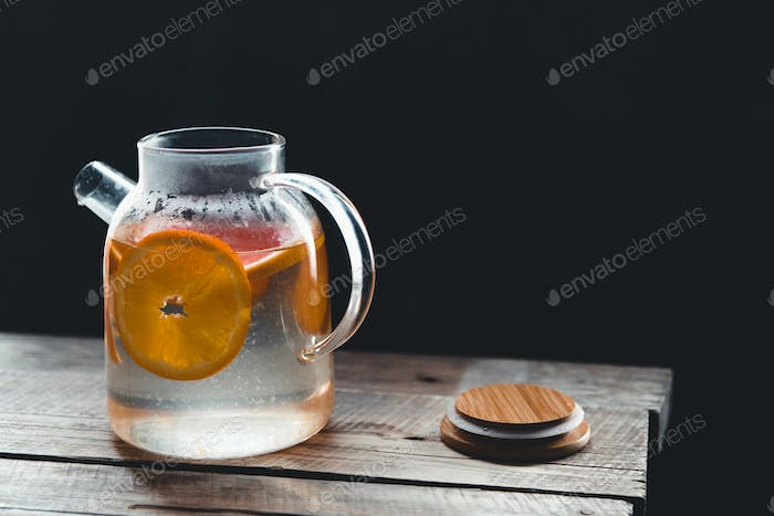 Citrus tea in a transparent teapot and a glass, healthy drink on a wooden background