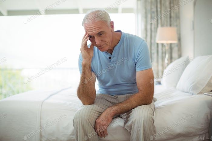 Stressed senior man sitting on bed