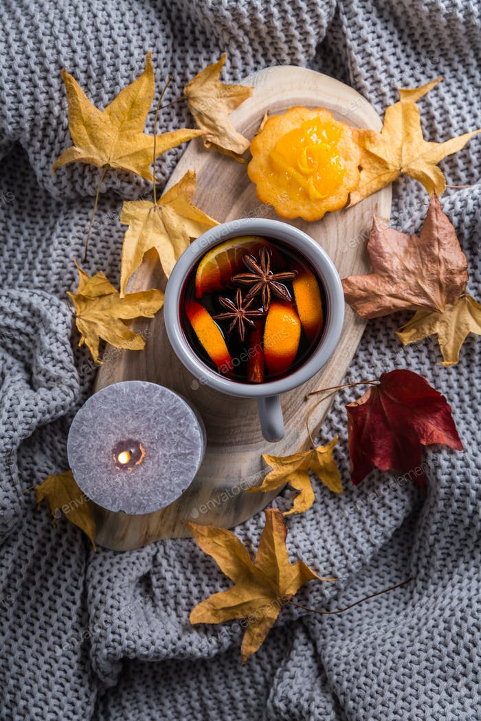 Cosy and soft winter background, with mulled wine, knitted blanket and candle with lemon cake