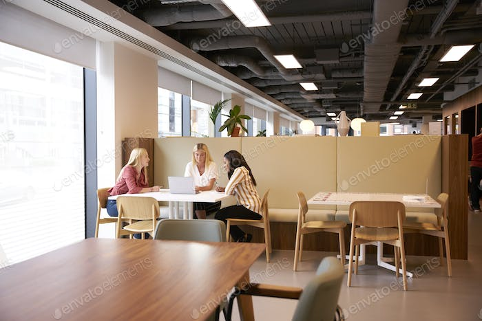Group Of Young Businesswomen Sitting Around Table And Collaborating On Task