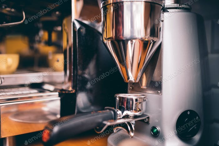 Professional coffee milling machinery preparing for espresso making