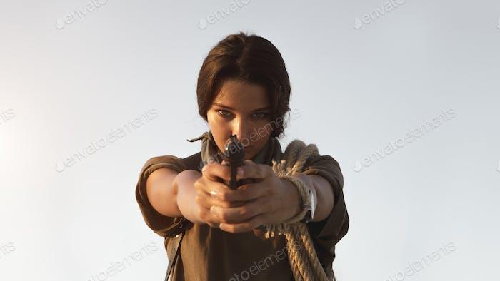 Frau stehend mit einem Gewehr im freien in der Wüste
