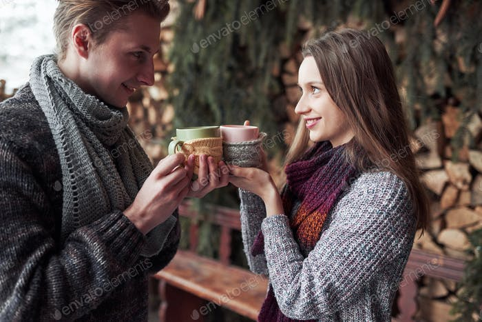 Young couple having breakfast in a romantic cabin outdoors in winter. Winter holiday and vacation