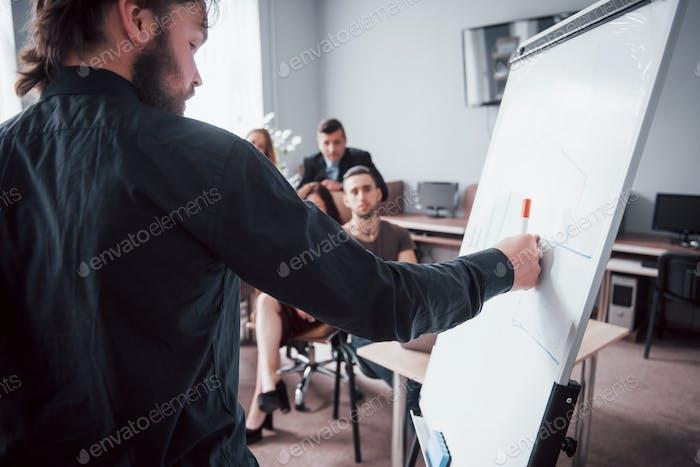Счастливые молодые коллеги обсуждают на встрече в креативном офисе