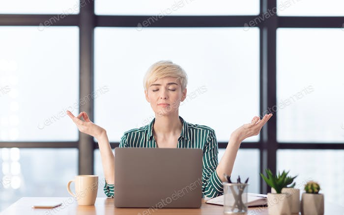 Peaceful Businesswoman Relaxing Meditating Sitting At Workplace In Office