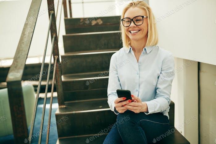 Lächelnde Geschäftsfrau sitzt auf der Treppe in einem Büro Senden von Texten