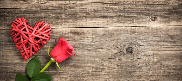 Red wicker heart and rose flower on wooden background