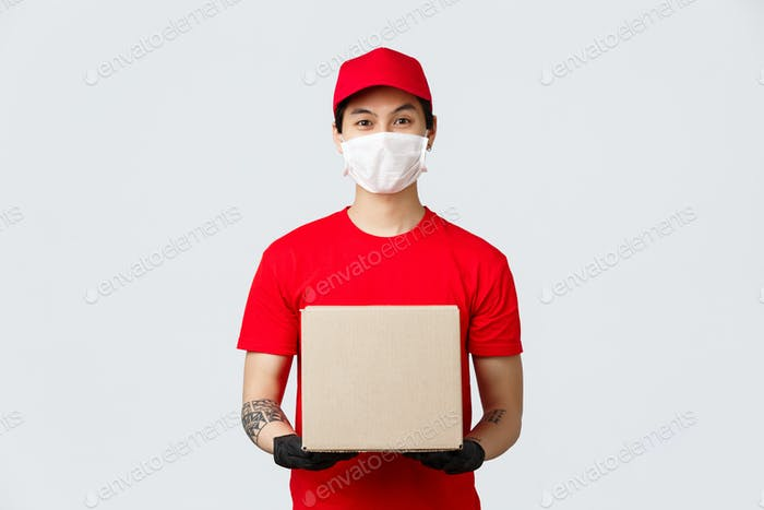 Friendly asian delivery guy with box parcel waiting for client open door. Courier in medical mask