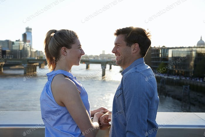 Romantic Couple Standing On Bridge Over River Thames In London