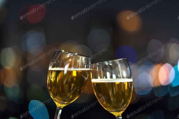 Tintineando con dos tazas de cerveza o vasos sobre la foto borrosa del paisaje urbano para celebrar