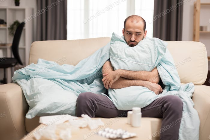 Man with fever wrapped on blanket