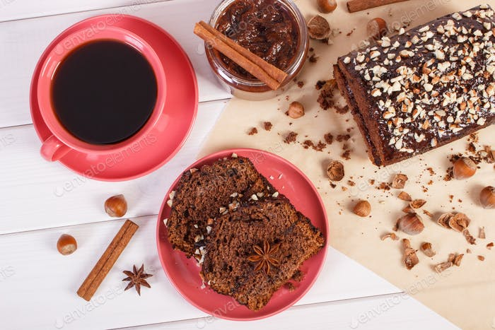 Dark cake with chocolate, cocoa and plum jam, cup of coffee, concept of delicious dessert