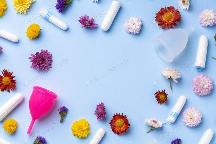 Menstrual cup and tampons on floral pattern background