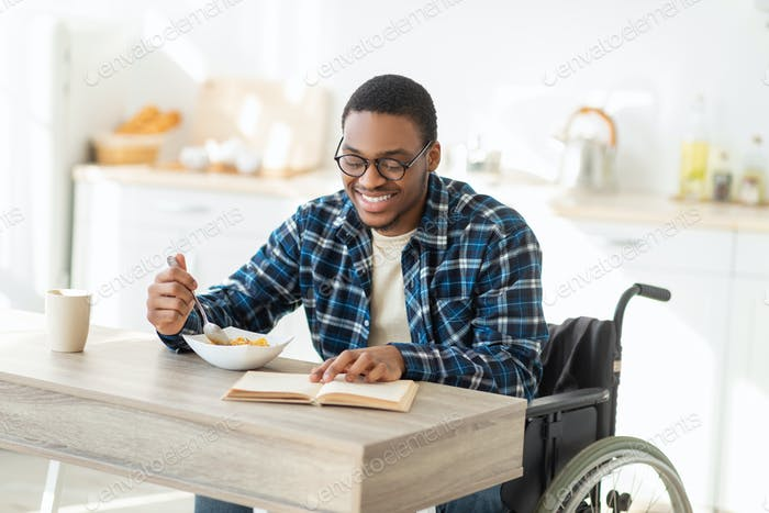 Positive black impaired guy in wheelchair having breakfast and reading interesting book at kitchen