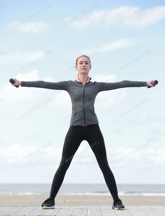 Sporty young woman exercising with weights