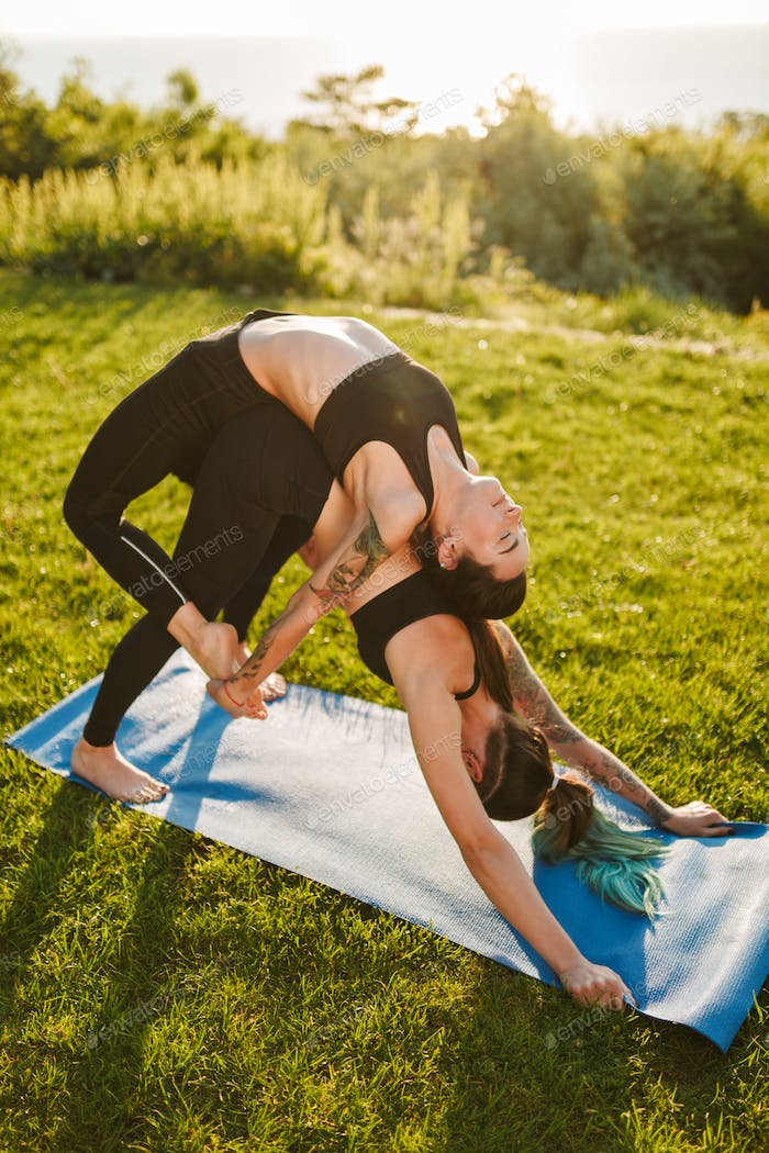 Two beautiful ladies in black sporty tops and leggings training yoga poses together on mat