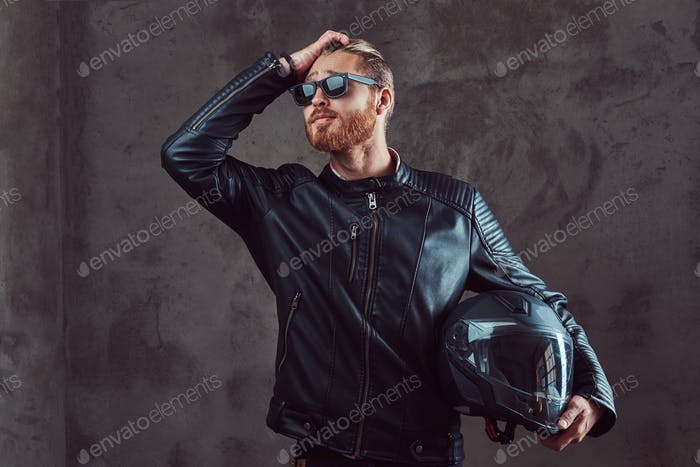 Portrait of a handsome stylish redhead man in a black leather jacket, posing in a studio