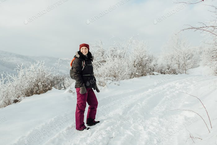 Smiling woman dressed warm enjoying a walk in snowy country