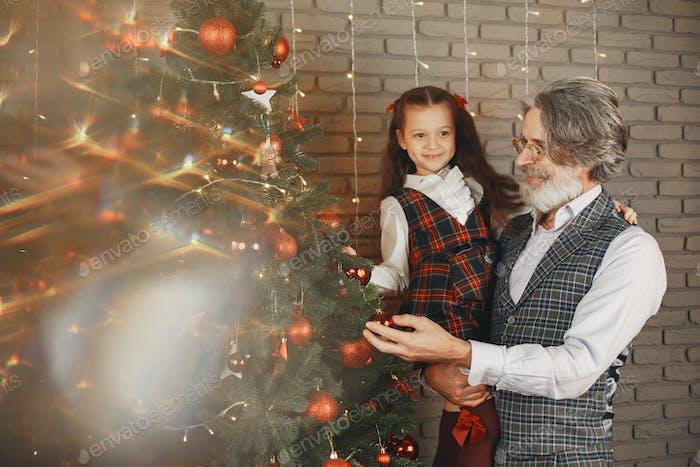 Lächelnder Großvater und Enkelin schmücken das Christmass