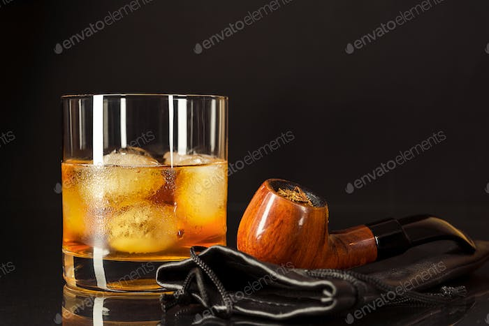 Scotch drink glass and smoking pipe on black background