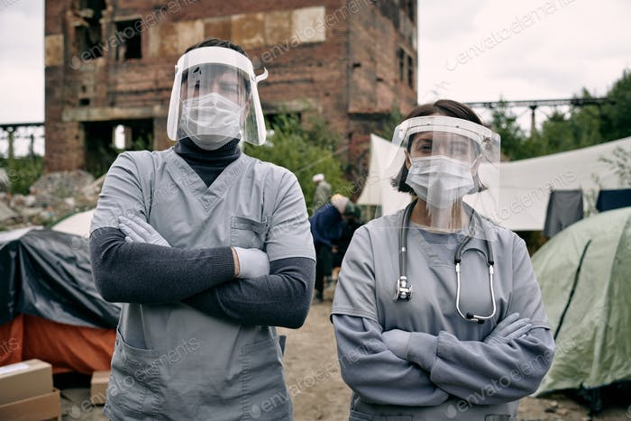 Two clincians in protective workwear standing in refugee camp