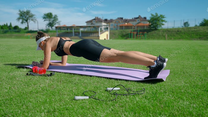 Woman practicing plank position at stadium field