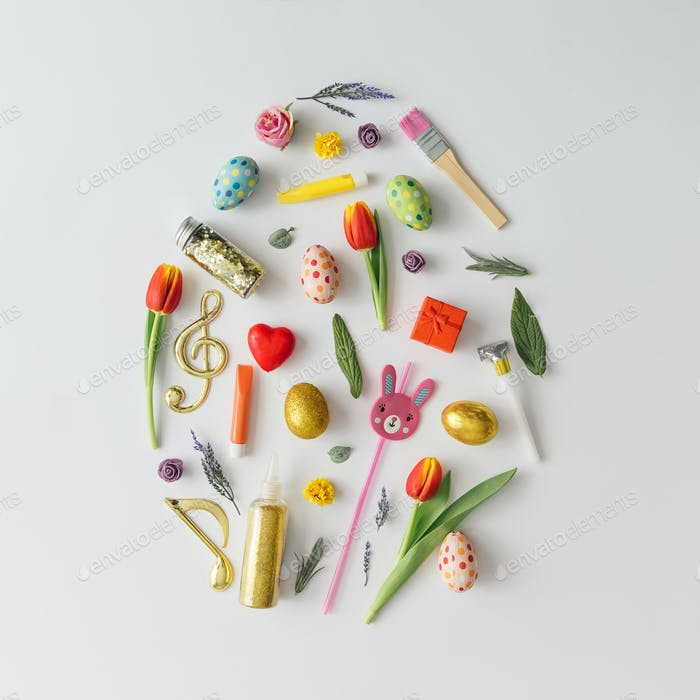 Easter egg shape made of various Easter decorative elements. Minimal spring concept. Flat lay.