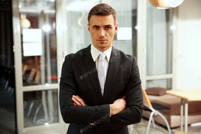 Confident businessman standing with arms folded at office