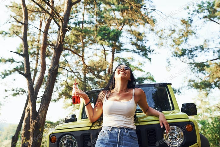Blonde with alcohol in hand have a walk in the forest against green jeep