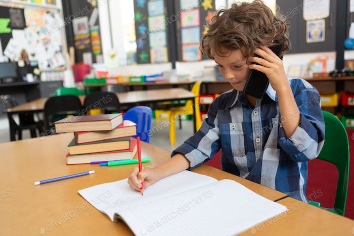 Schoolboy talking on mobile phone at desk in the classroom at school