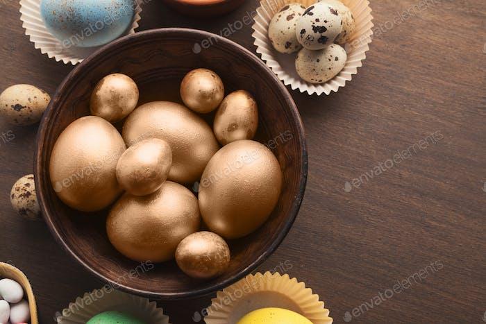 Golden easter eggs in wooden bowl