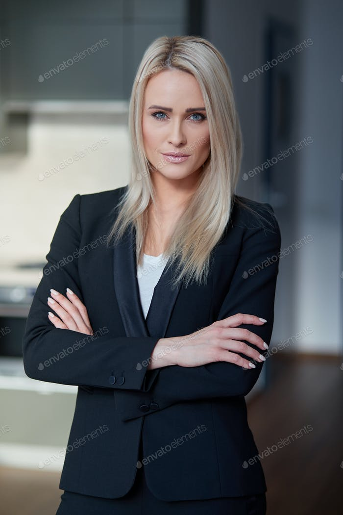 Nice and calm blond, middle age business woman standing at her office