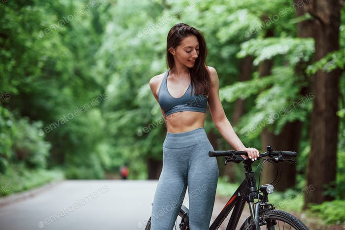 Caucasian ethnicity. Female cyclist standing with bike on asphalt road in the forest at daytime