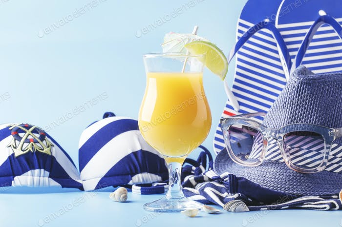 summer beach things in nautical style for vacation with orange cocktail