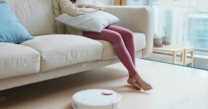 Frau heben die Füße mit Roboter-Vakuum auf dem Boden zu Hause