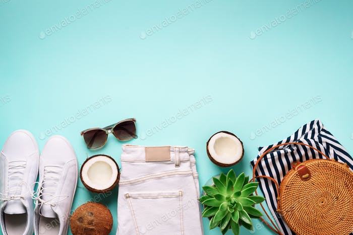 Woman summer travel clothes travel on blue background. Jeans, sneakers, bamboo bag, sunglasses