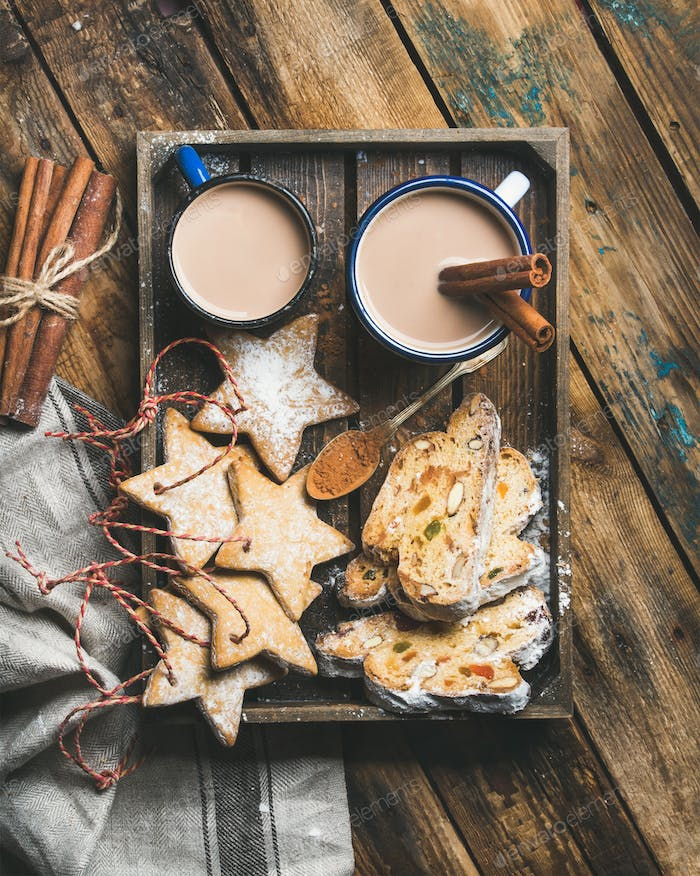 Cocoa in mugs with Christmas cookies, pieces of Stollen cake