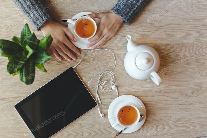 Mädchen sitzt am Tisch und trinkt grünen Tee. Ansicht von oben