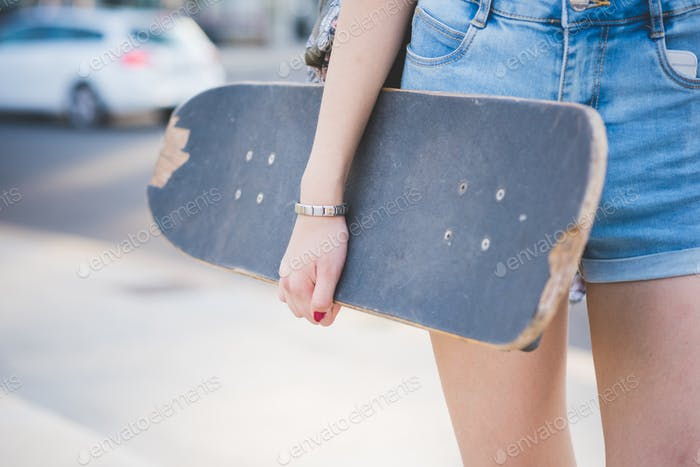 Close up on the hand of young woman holding a skateboard - sport