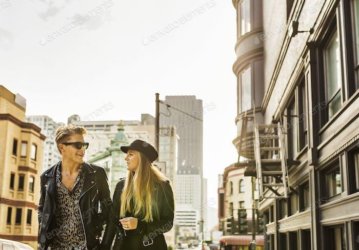 Junge Mann und Frau zu Fuß in der Stadt und im Gespräch