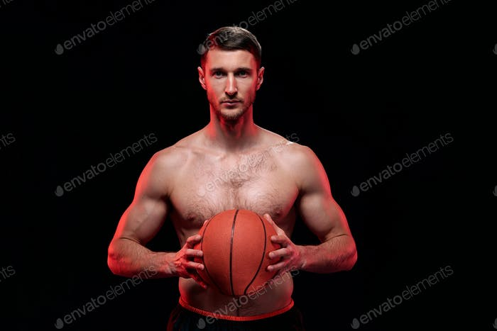 Young shirtless muscular basketball player holding ball by his chest