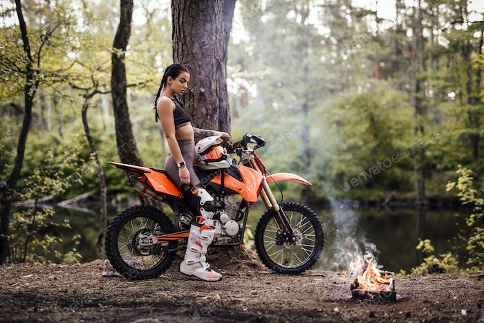Encantador joven mujer corredor que lleva traje de motocross con torso semi desnudo sentado en su bicicleta