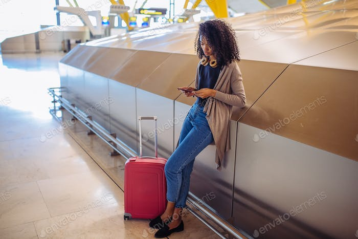 woman waiting her flight using mobile phone at the airport